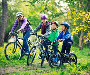 Mother with three kids riding bicycles in forest or park on sunny spring day. The boys are aged 6 and the girl is aged 10. Kids are smiling and having a good time.