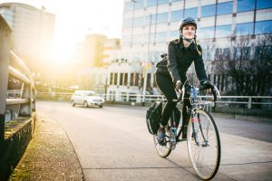 A smiling young woman commuting in an urban city environment on her street bicycle, waterproof panniers on her bike rack. She rides up a ramp from downtown Portland, Oregon, that leads up to the Burnside bridge. Colorful sky from the setting sun. Horizontal image with copy space.